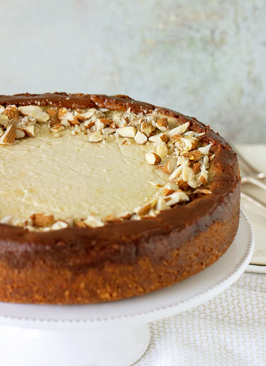 Partial image of whole brown sugar cheesecake on white cake stand