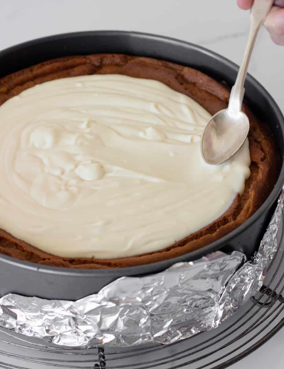 Smoothing topping on semi baked cheesecake, still in pan