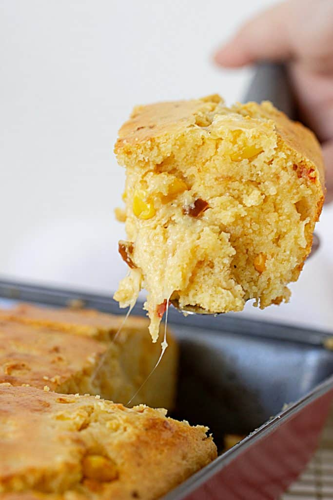 Taking a square of cheese cornbread from pan