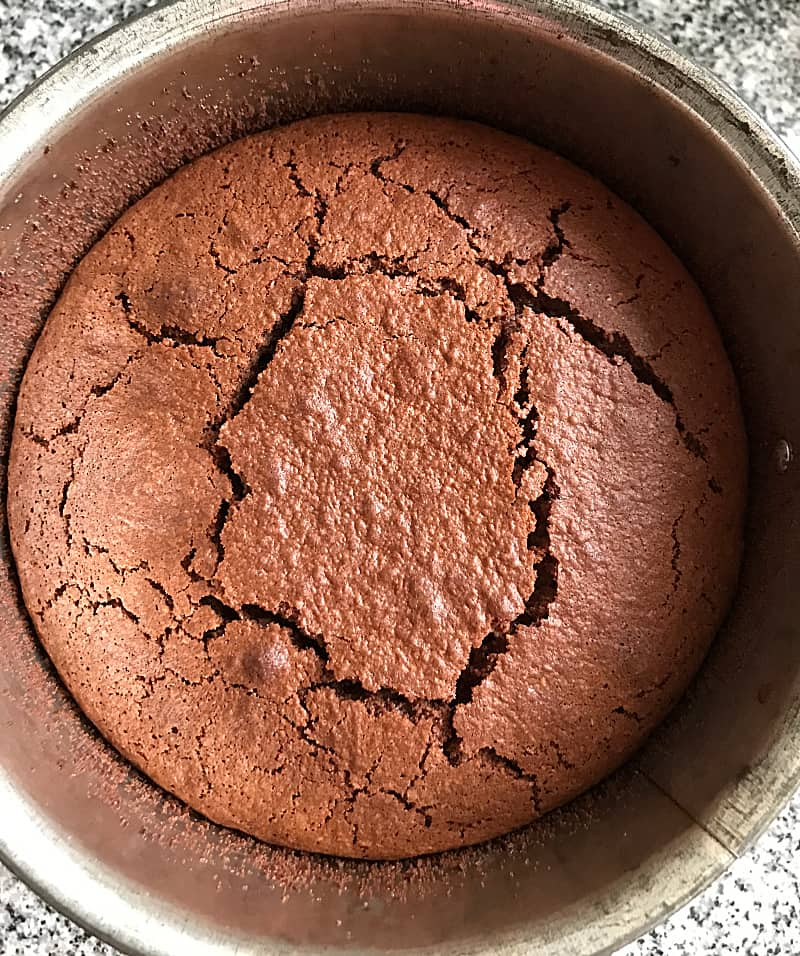Baked flourless chocolate cake in metal pan, crackly top