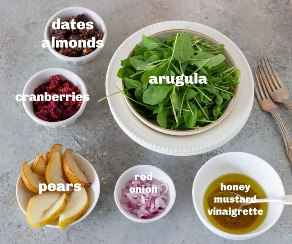 Pear Arugula Salad ingredients in bowls on grey surface