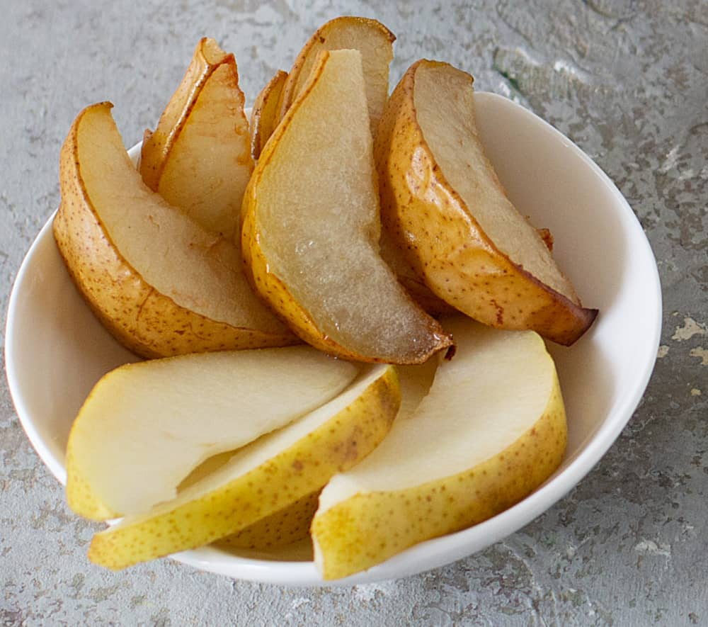 Raw and baked pear wedges on white bowl, grey surface