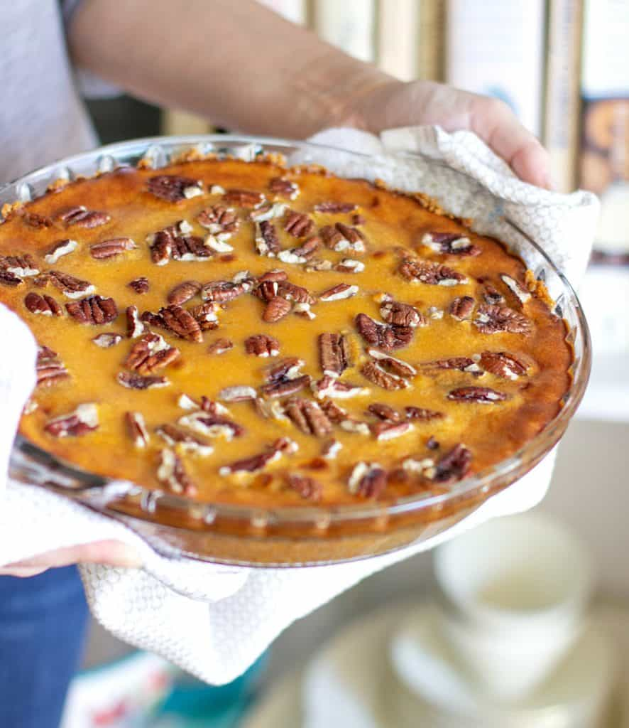 Hands holding glass dish with sweet potato pie with a kitchen towel