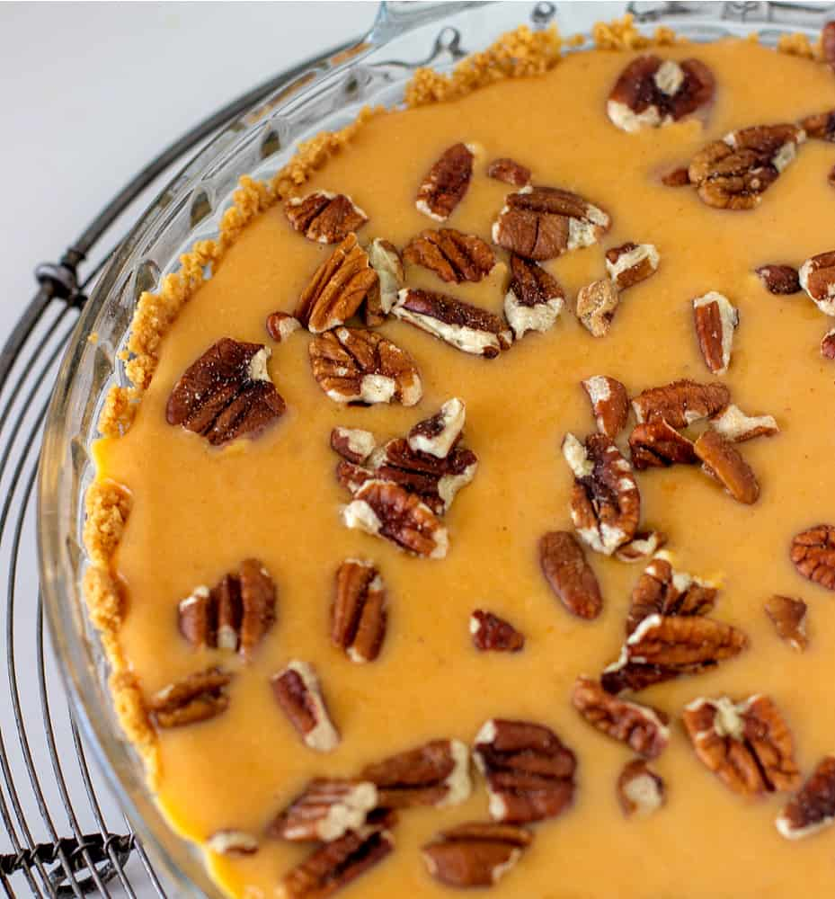 Partial image of unbaked sweet potato pie on wire rack