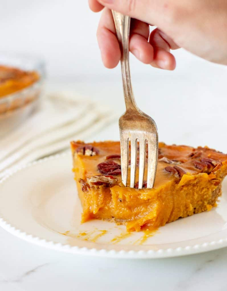 Hand with fork in piece of sweet potato pie on a white plate