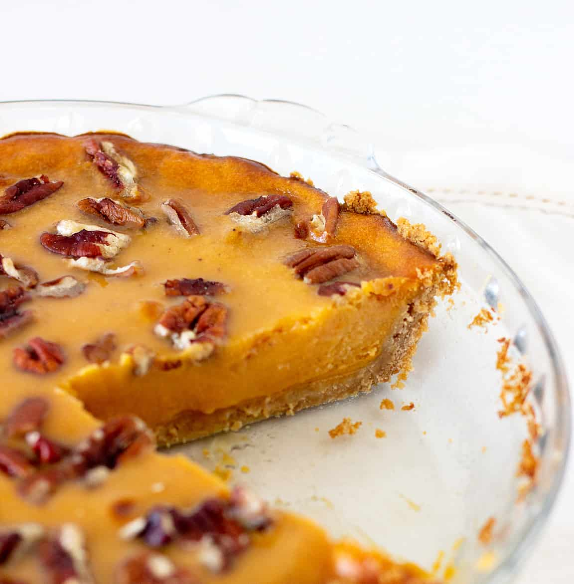 Partial view of cut sweet potato pie in glass pie dish, white surface