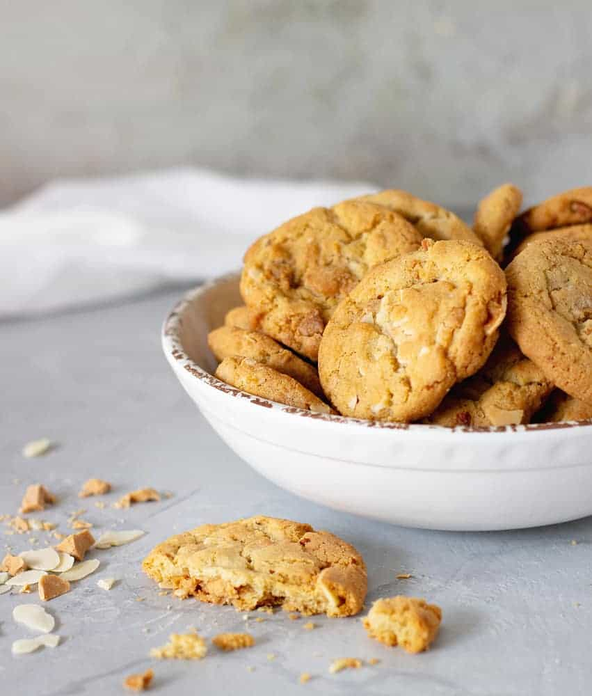 White bowl of cookies, grey background, white cloth, broken cookie