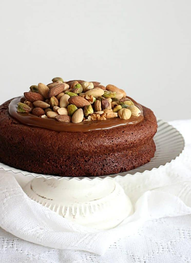 Whole chocolate cake topped with caramel and nut on a white cake stand
