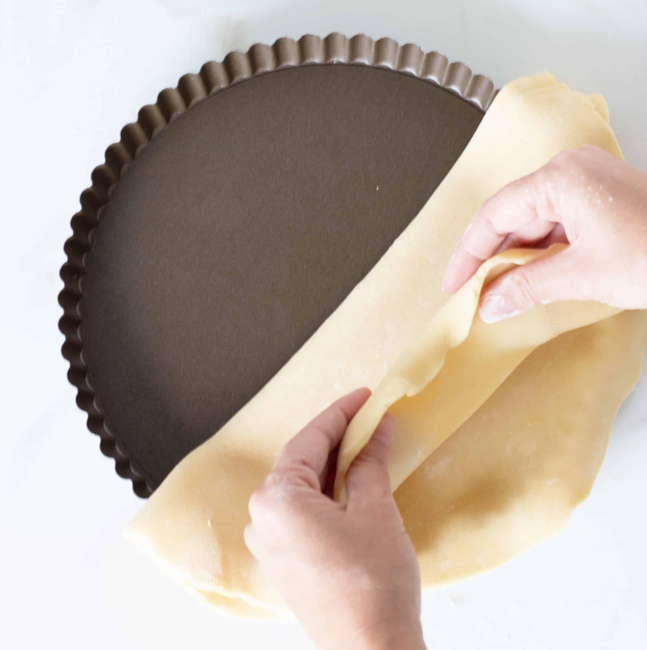 Hands lining dark metal pie pan with pie crust
