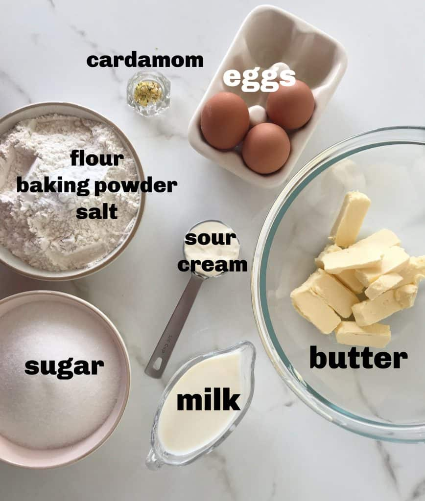 Cardamom Cake ingredients in bowls on white surface