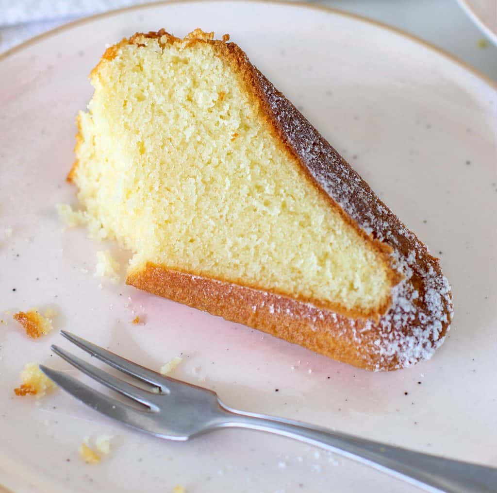 Slice of bundt cake on light pink plate with fork