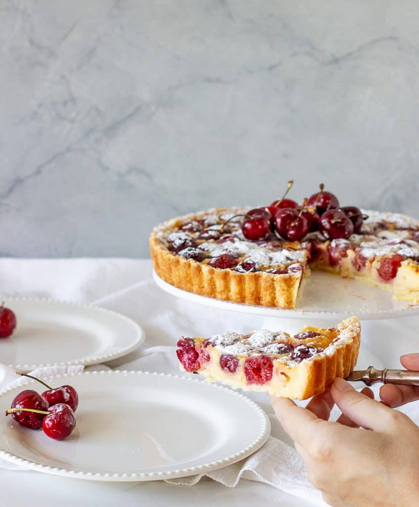 Serving slice of cherry pie on white plate, tart on cake stand, white background