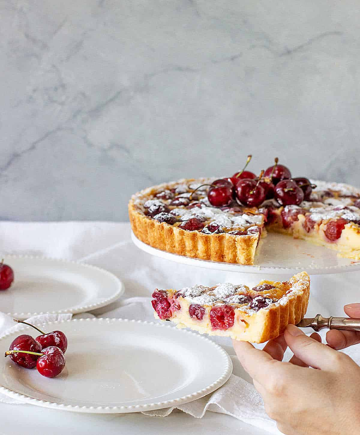 Serving a slice of cherry pie on white plate, tart on cake stand, white background