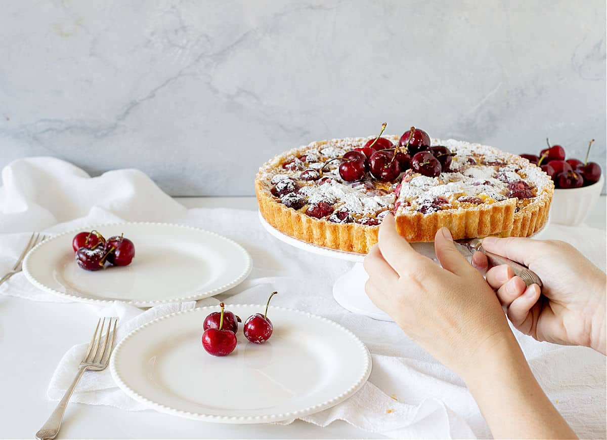 White surface with white plates, cherries, hands cutting whole tart on cake stand