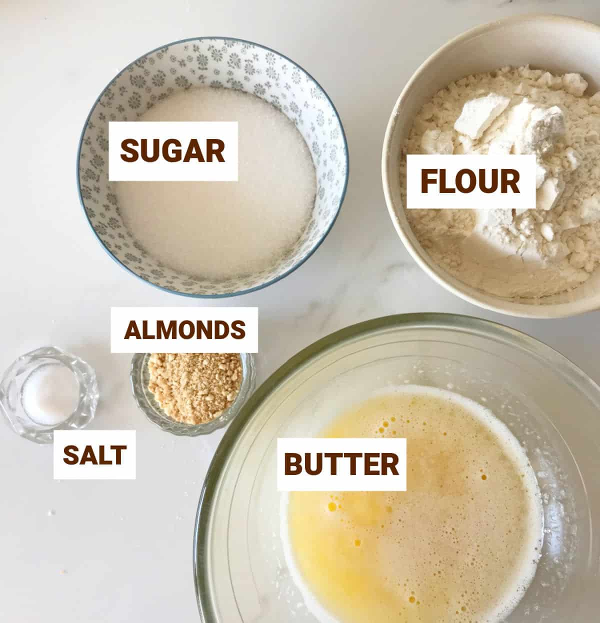White surface with bowls containing ingredients for pie crust including almonds, salt, butter