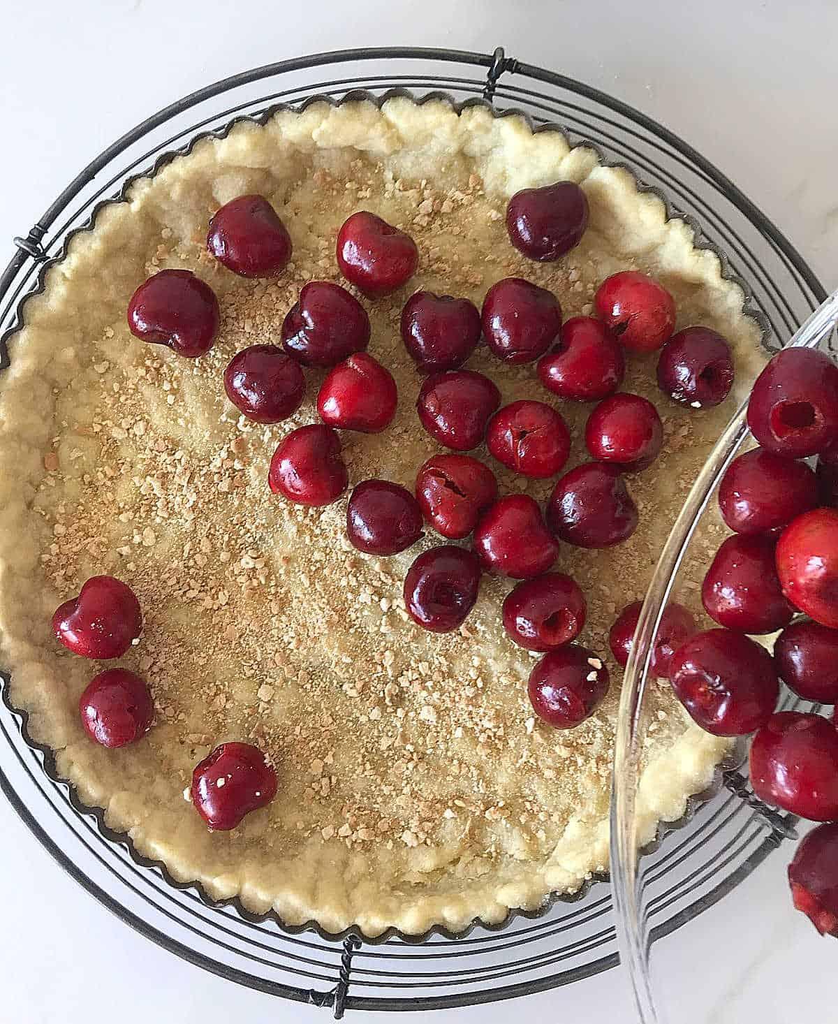 Filling tart crust with fresh cherries, white surface