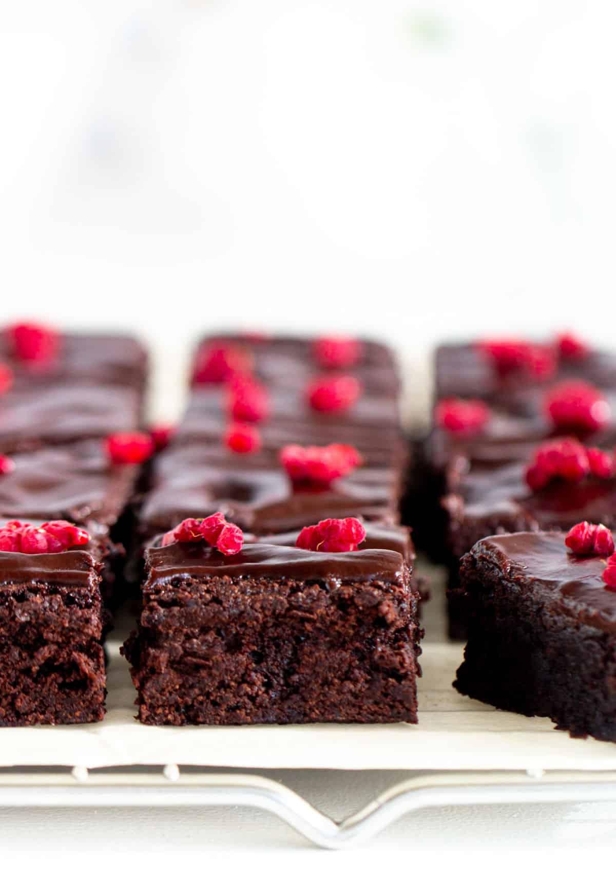 Frontal view of three rows of brownies, raspberries on top, on beige paper and rack