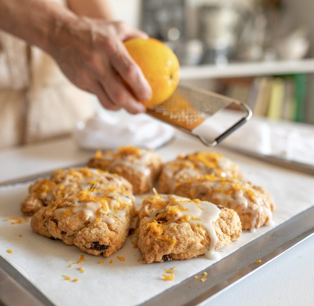 Grating orange peel over glazed scones on white table