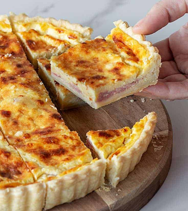 Hand lifting square of ham and cheese quiche on wooden board