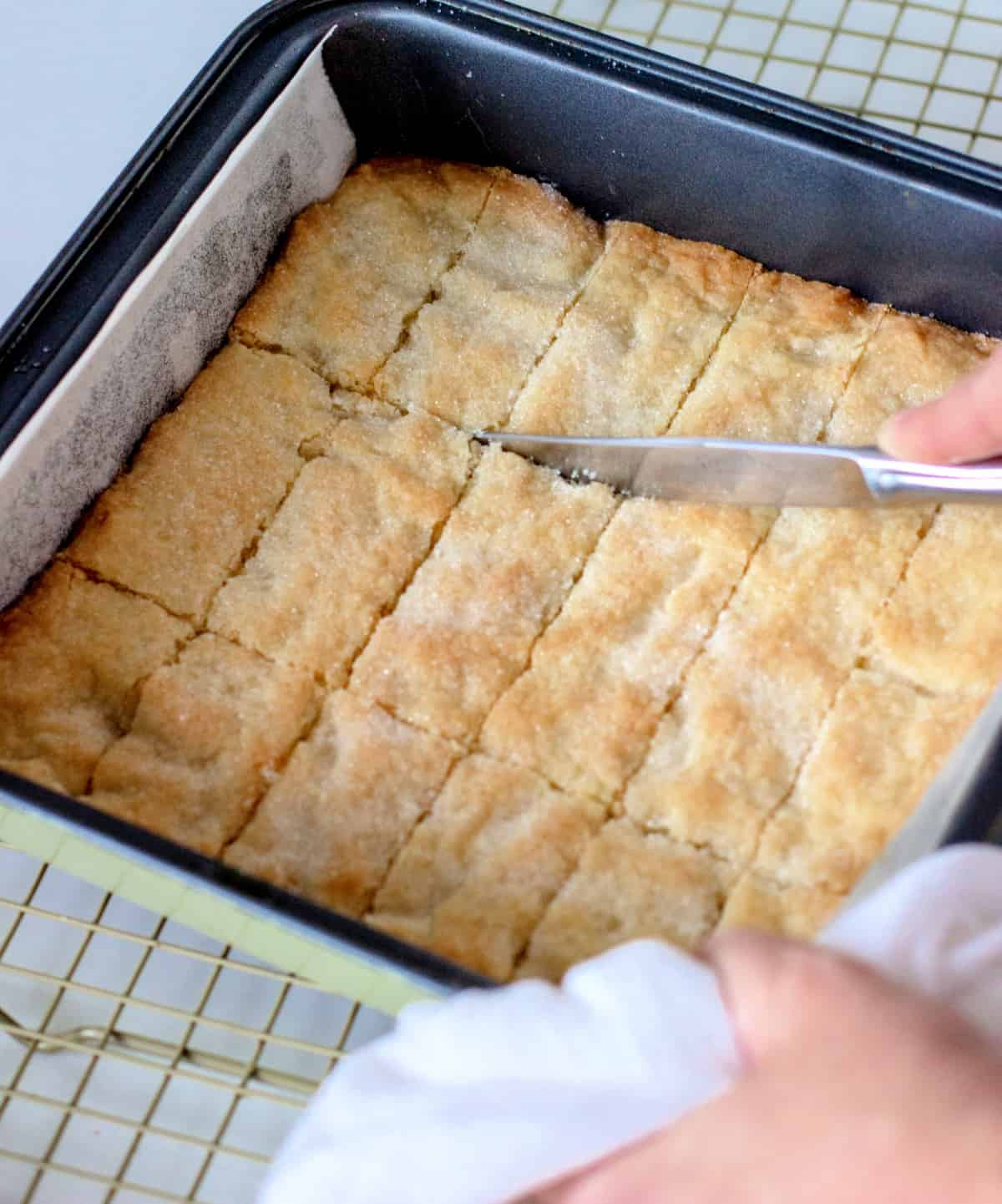 Cutting baked shortbread with a knife in the metal square pan