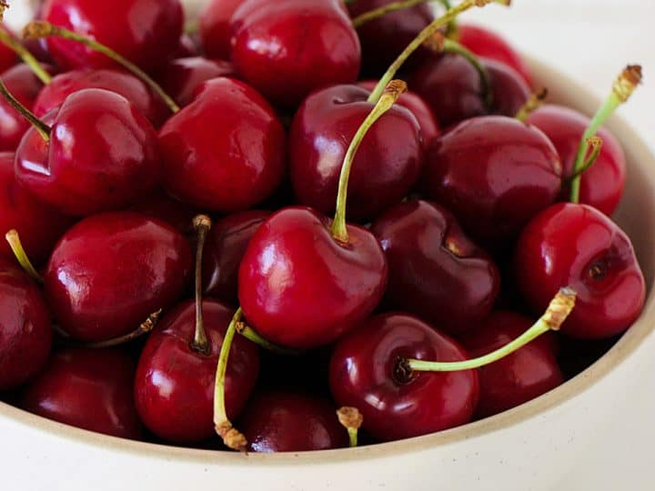 White bowl of fresh cherries