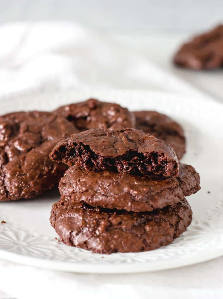 Stack of brownie cookies on white plate, white background