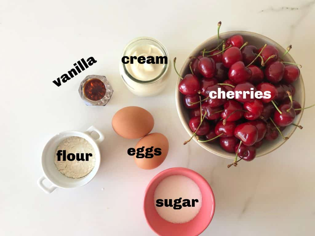 Cherry custard filling ingredients in bowls on white surface