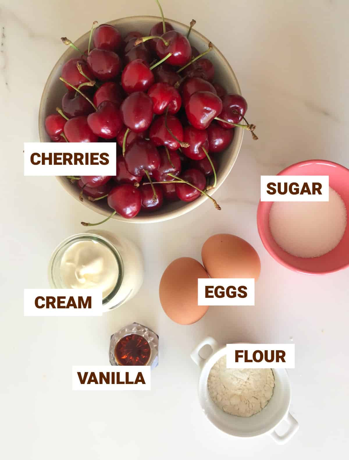 Cherry custard filling ingredients in bowls on white surface including cream, eggs, vanilla