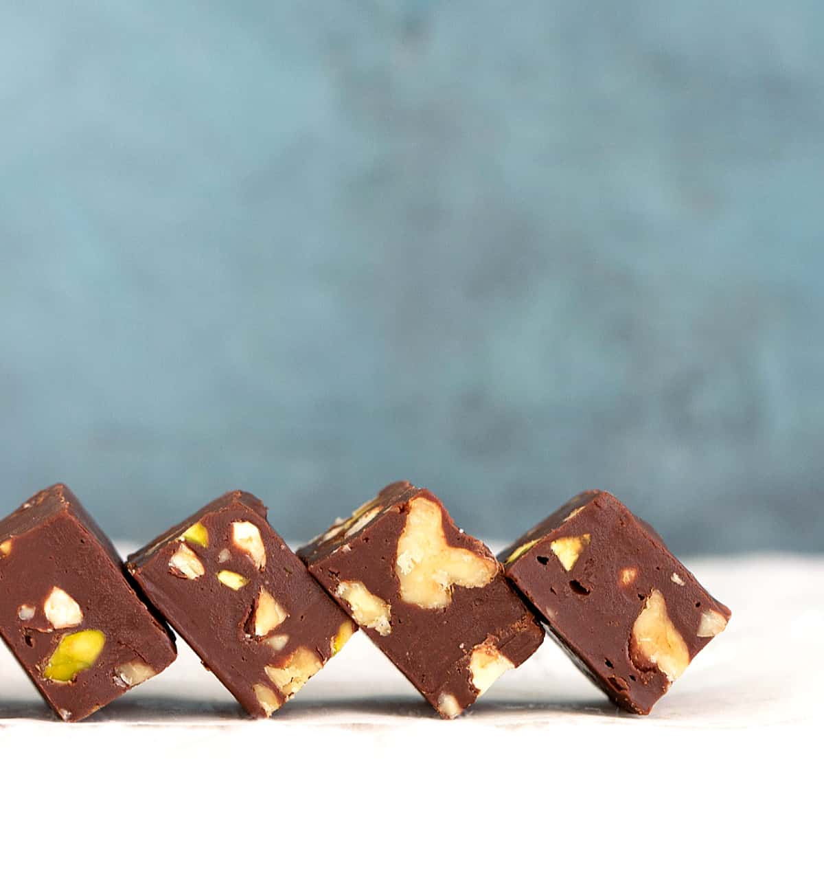 Row of chocolate fudge squares on a white surface and blueish background