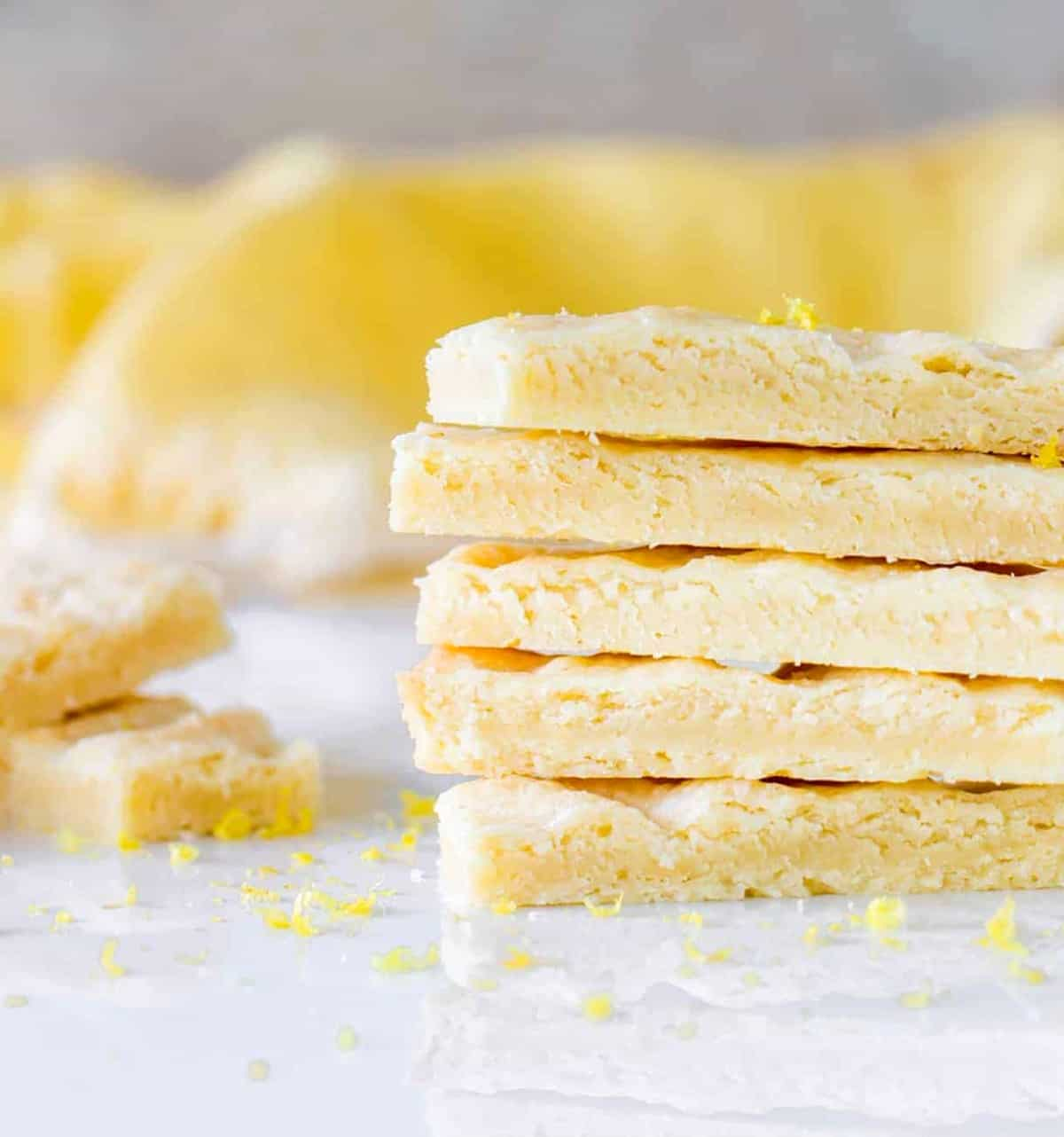 Lemon shortbread fingers stacked on white marble surface; yellow background