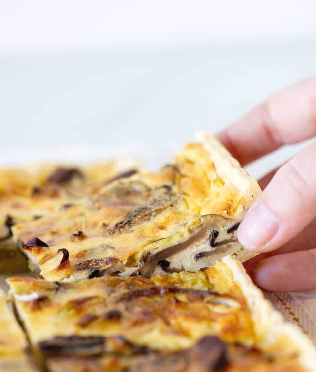 Hand lifting a piece of mushroom quiche