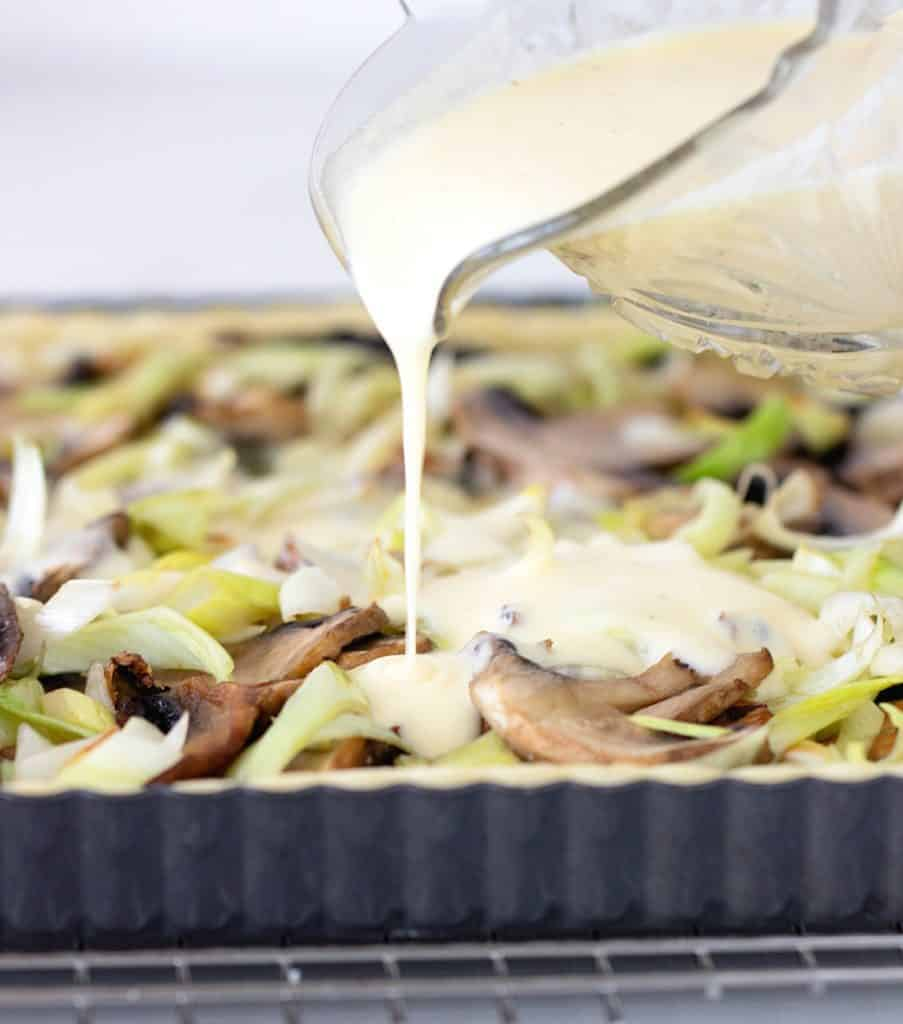 Pouring of binding cream over mushroom quiche filling