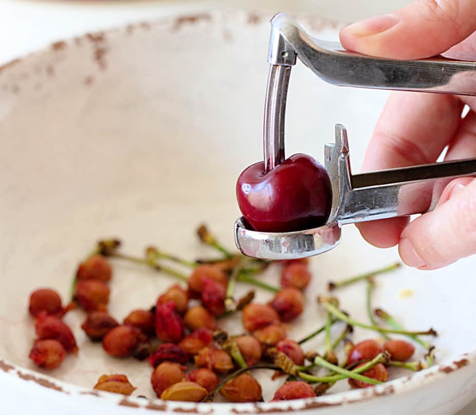 Hand with cherry pitter, whole cherry, white bowl with pits