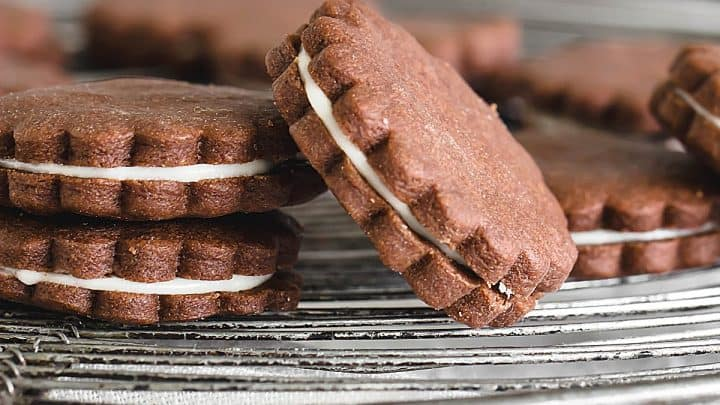 Round chocolate sandwich cookies on wire rack