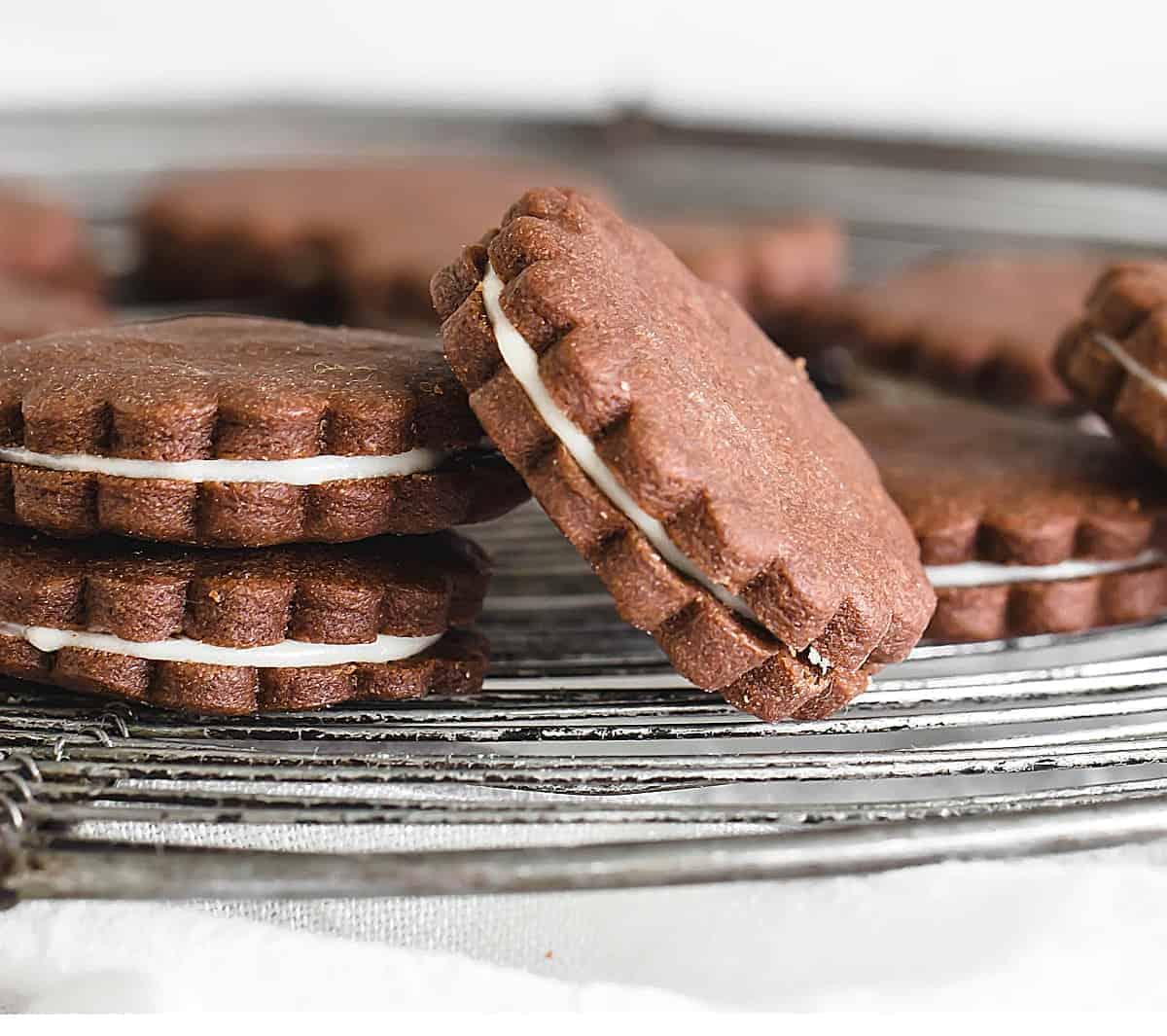 Round chocolate cookies with white filling on wire rack