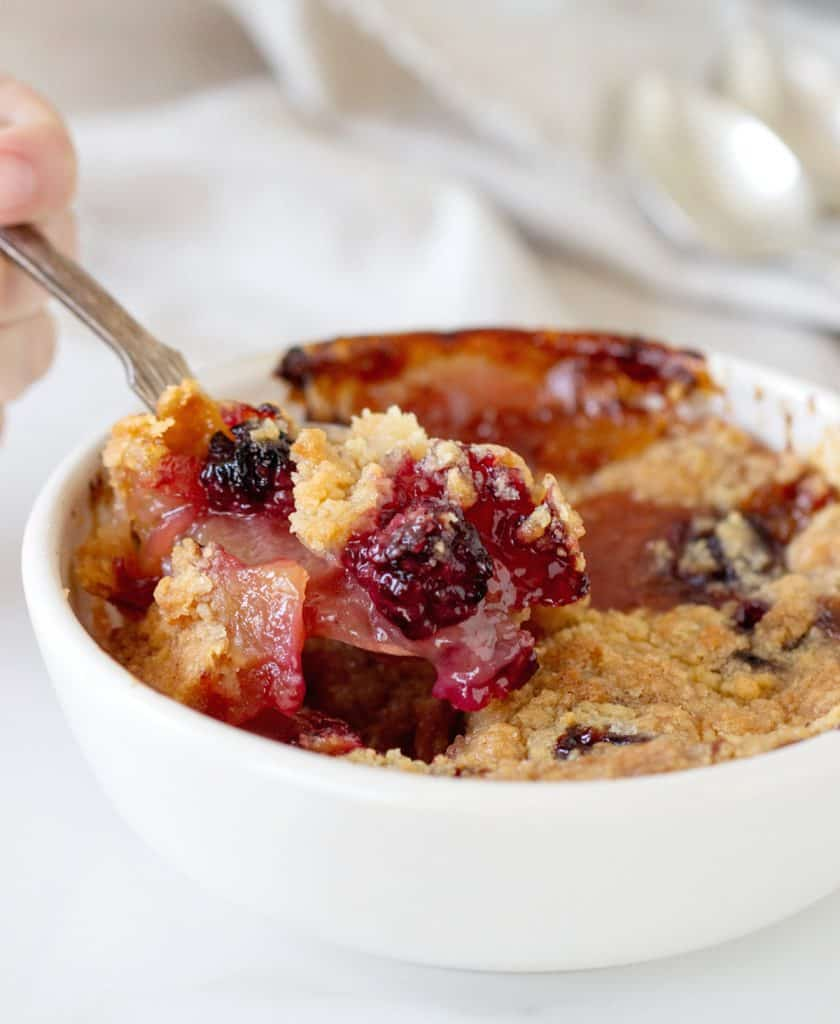 Spoon lifting apple blackberry crumble from white bowl
