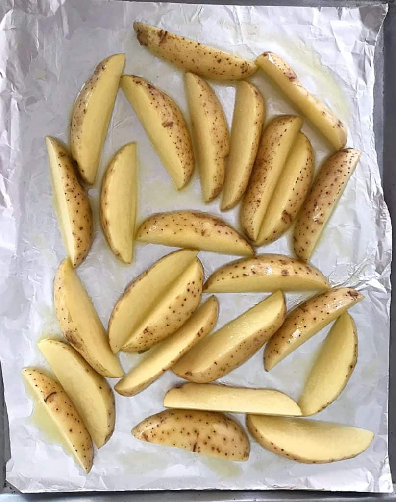 Oiled raw potato wedges on aluminum paper