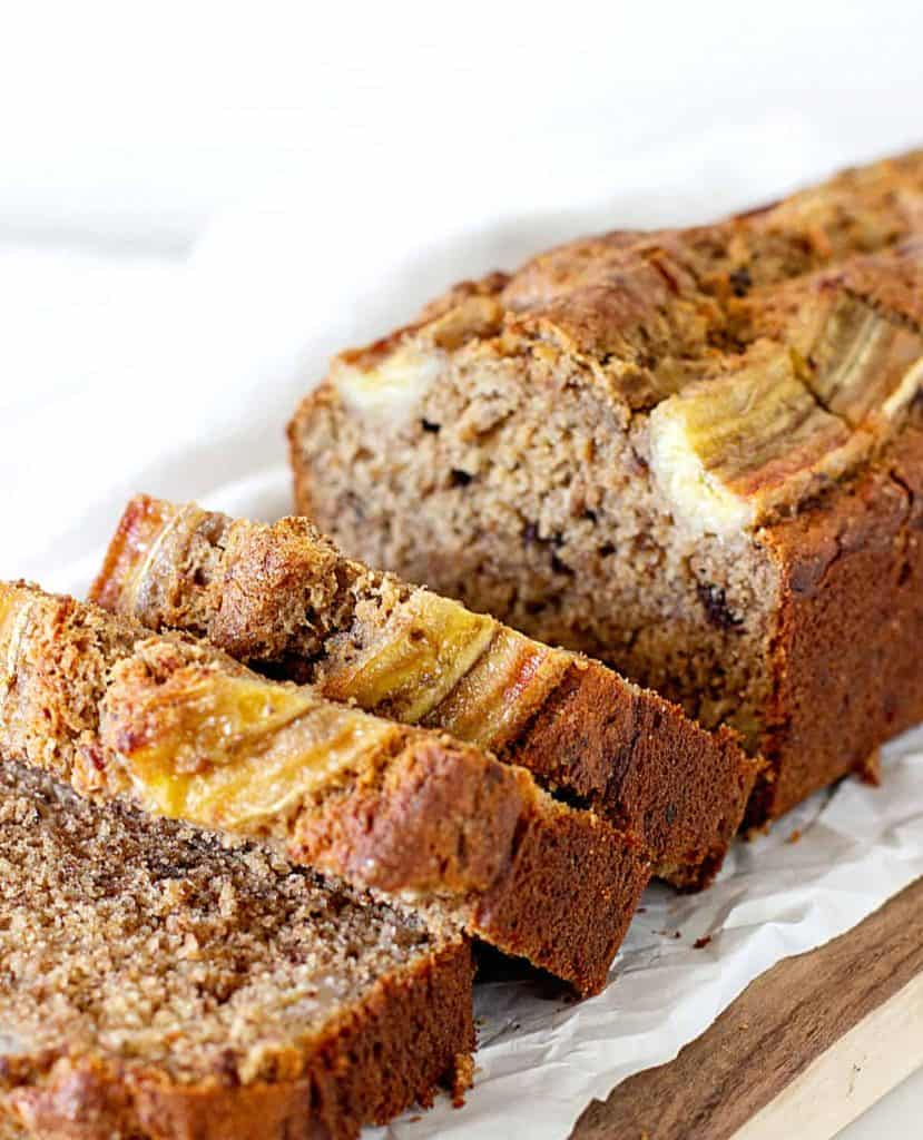 Sliced banana bread loaf on parchment paper