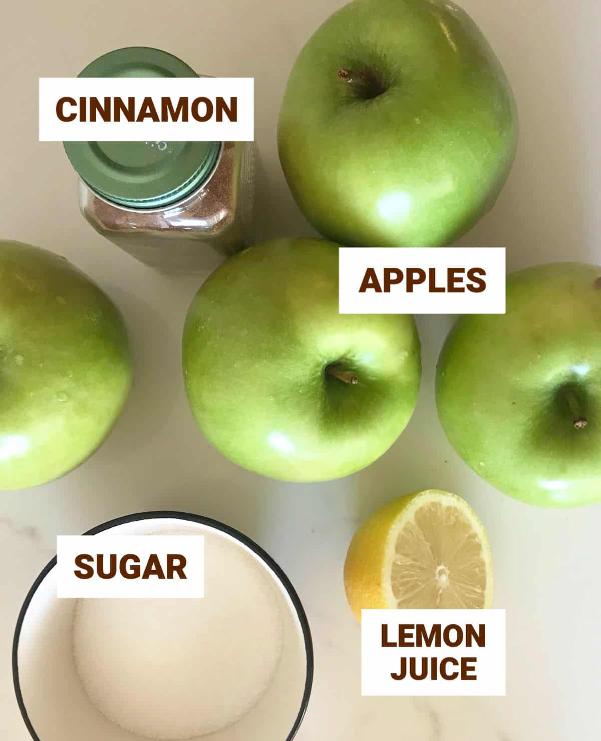 Green apples, half a lemon, and other ingredients ingredients on white surface