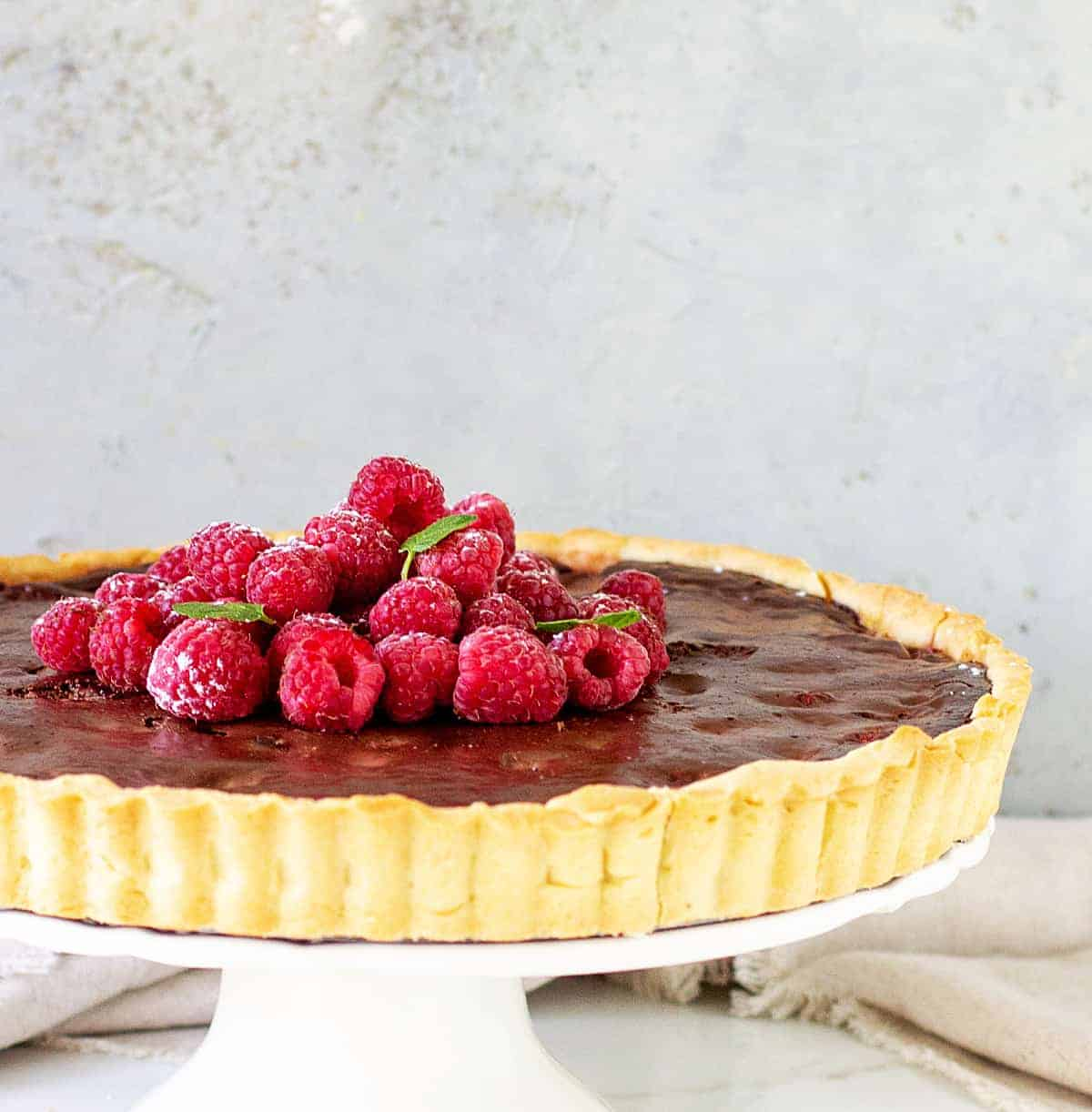 Partial image of chocolate tart on white cake stand, whole raspberries on top