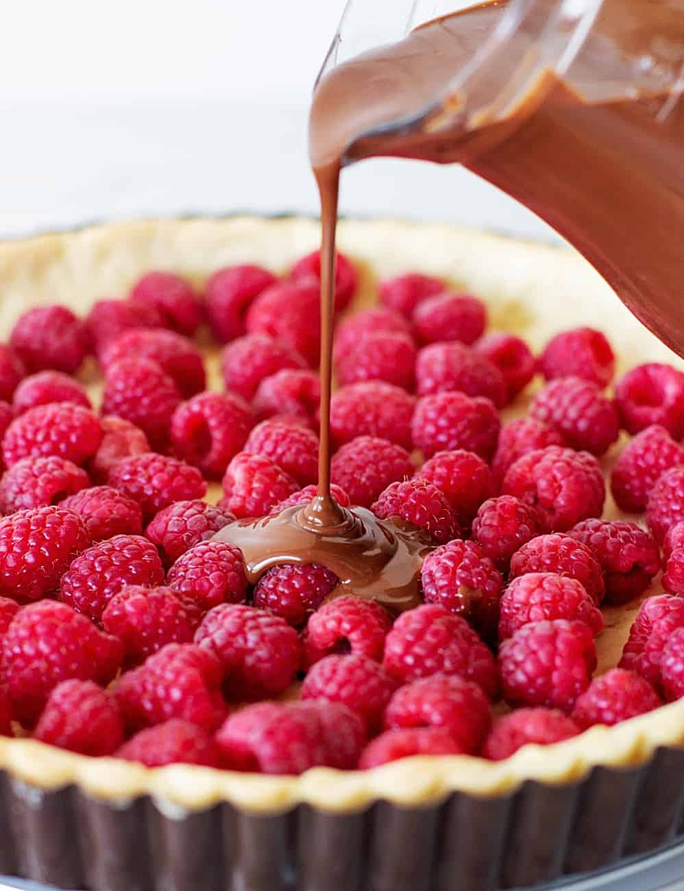 Pouring chocolate filling onto tart crust filled with fresh raspberries