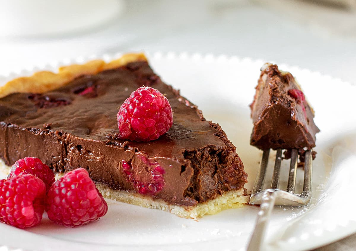 Close-up of slice of chocolate raspberry tart on white plate, silver fork with bite
