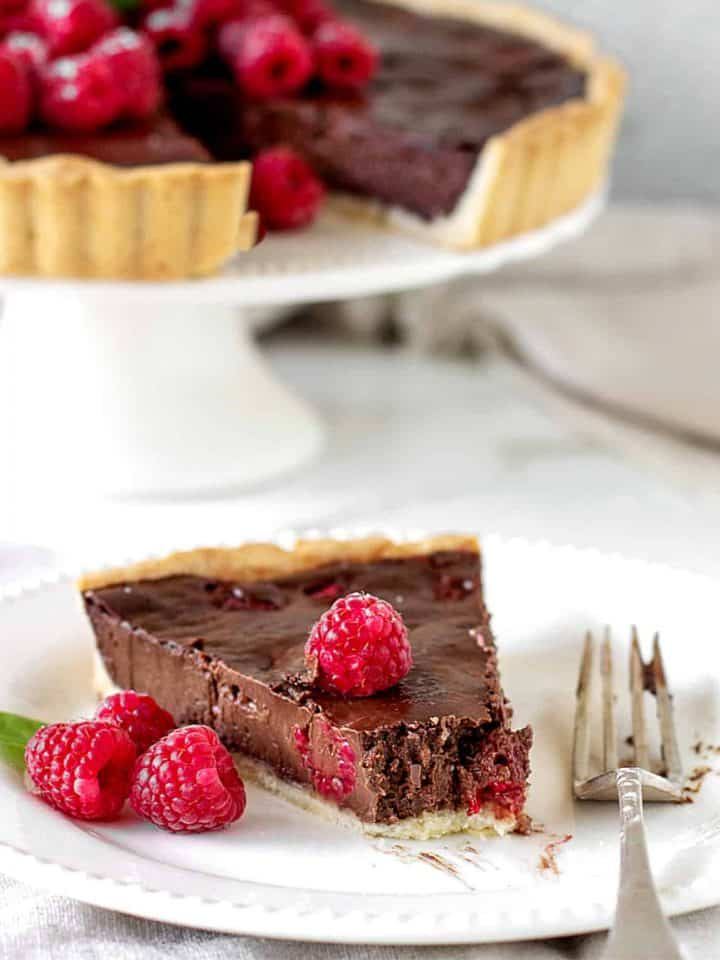 Slice of chocolate raspberry tart with missing bite, on white plate, silver fork