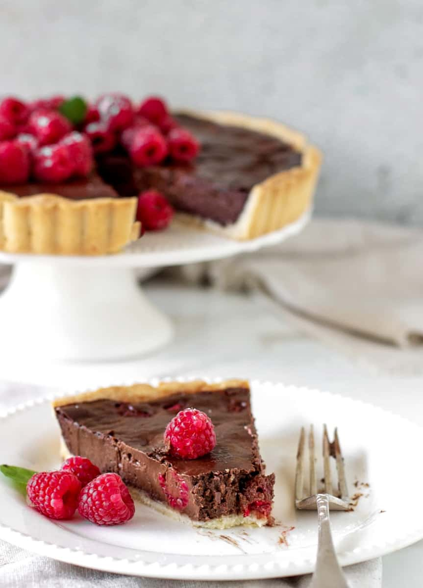 Vertical image of chocolate raspberry tart in background, a slice on a white plate, silver fork