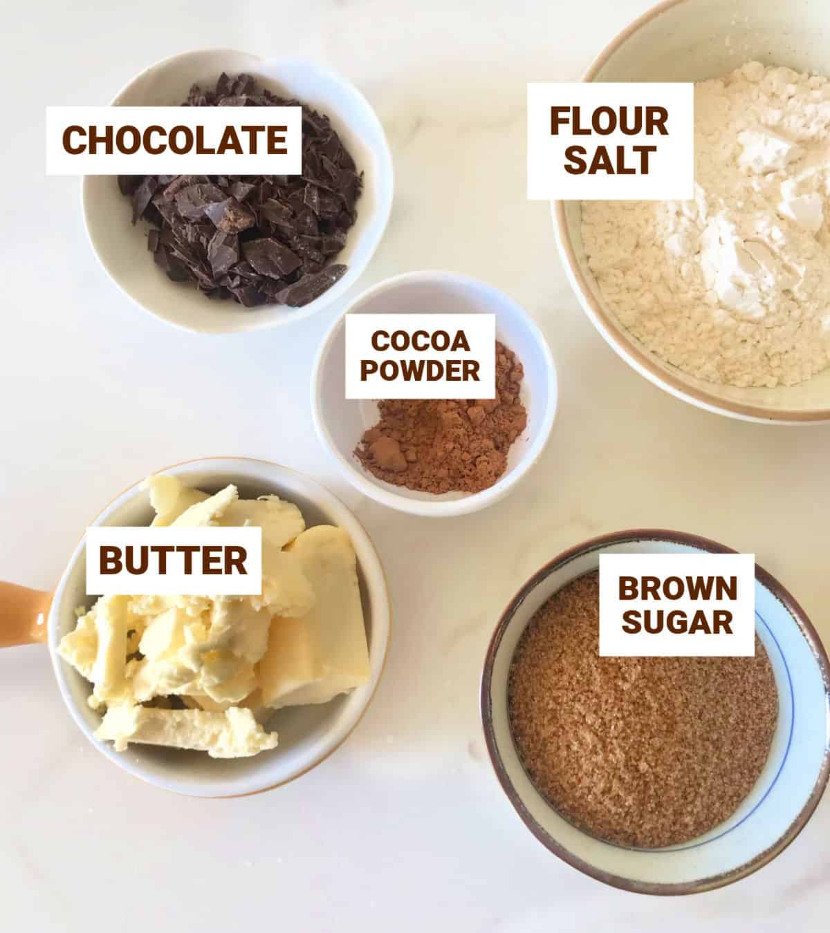 Chocolate crumble ingredients in different sized bowls on white surface