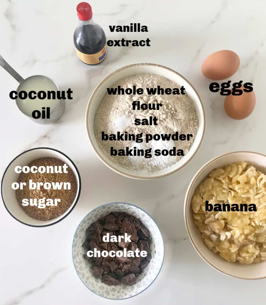 Banana chocolate bread ingredients in bowls on white surface