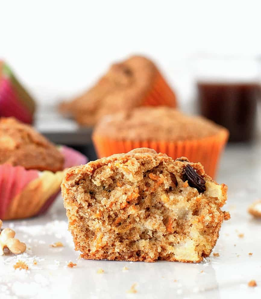 Single half muffin on white surface, whole colorful muffins on background