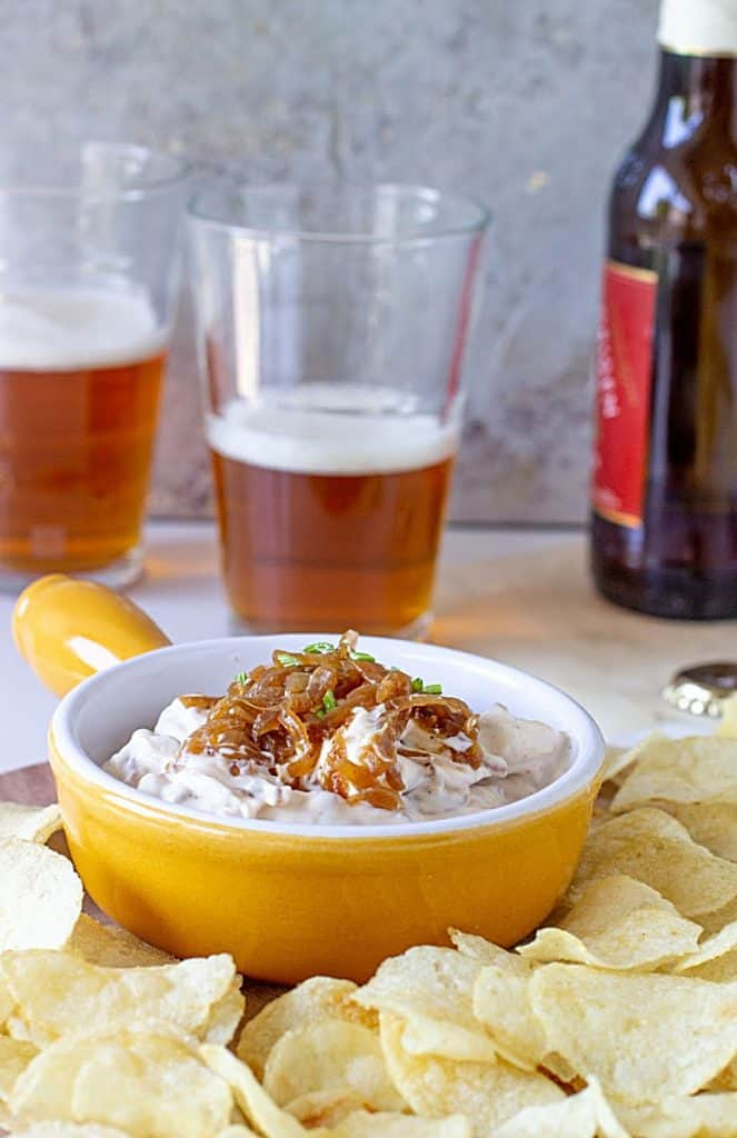 Yellow shallow bowl with Onion Dip surrounded by potato chips and beer