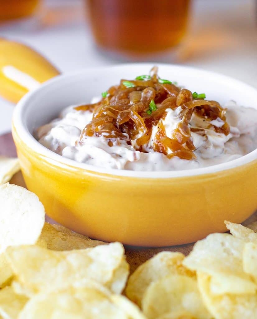 Yellow shallow bowl with onion dip, potato chips around