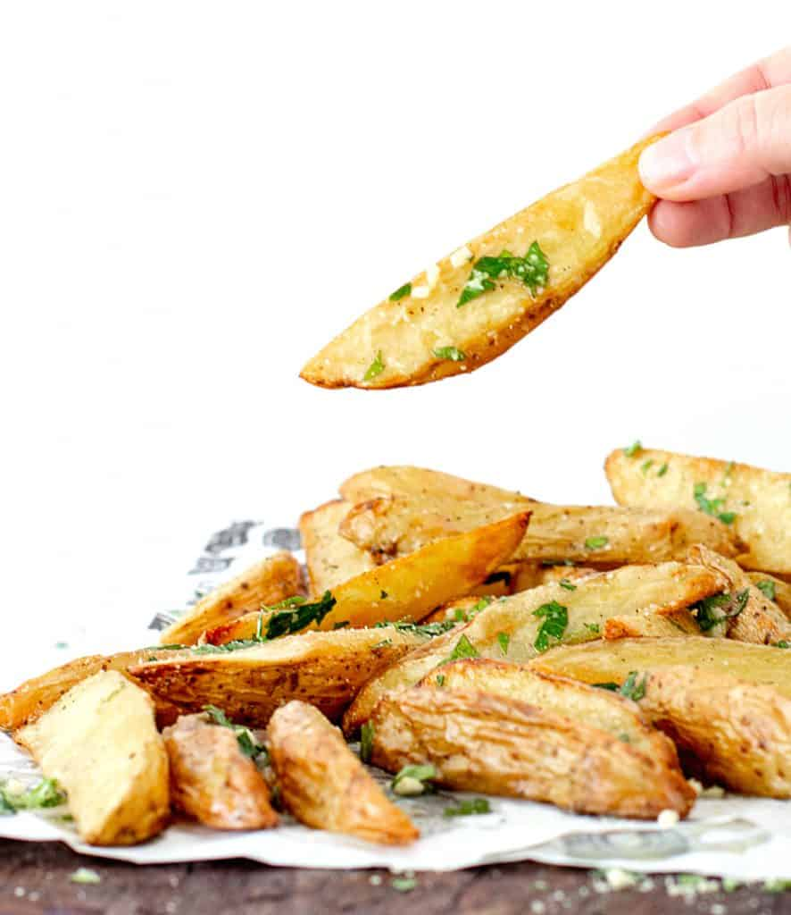 Hand holding potato wedge beneath a mound of potato wedges on a wooden board